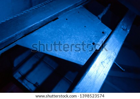 Blade of a guillotine lit with blue light #1398523574