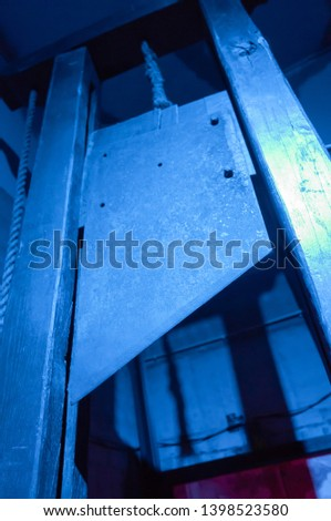 Blade of a guillotine lit with blue light #1398523580