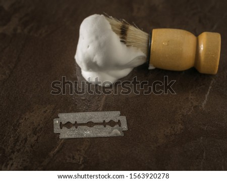 Blade shaving brush shaving with lather on the stone background. Set for care of a man's face.