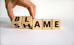 Blame or shame. Male hand flips wooden cubes and changes the inscription 'shame' to 'blame' or vice versa. Beautiful white background, copy space.
