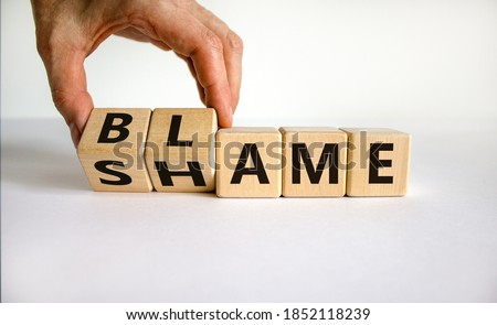 Blame or shame. Male hand flips wooden cubes and changes the inscription 'shame' to 'blame' or vice versa. Beautiful white background, copy space. Сток-фото ©