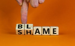 Blame or shame. Male hand flips wooden cubes and changes the word 'shame' to 'blame' or vice versa. Beautiful orange background, copy space. Blame or shame concept.