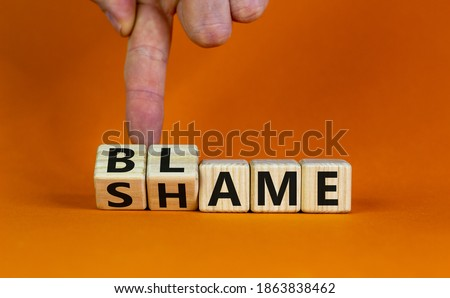 Blame or shame. Male hand flips wooden cubes and changes the word 'shame' to 'blame' or vice versa. Beautiful orange background, copy space. Blame or shame concept. Сток-фото ©