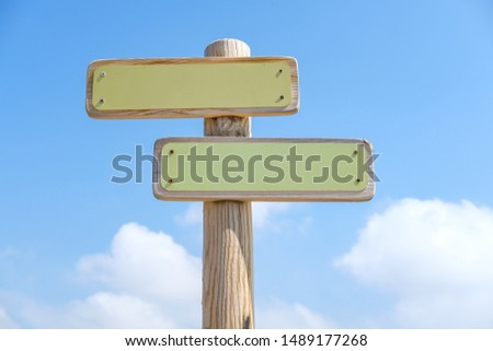 Blanc wooden signs in two directions on a pole with a blue sky and some clouds in background. Directional sign mock up of blank wood. #1489177268