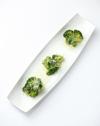 Blanched broccoli with sauce, mini portion. Vegetables on white plate. Diet food, minimum calories. Object isolated on white background.