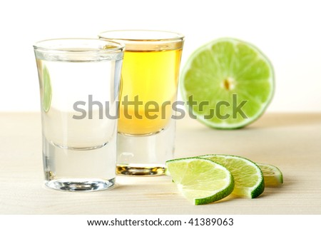 Blanco and Gold Tequila with lime slices on wood table isolated on white background