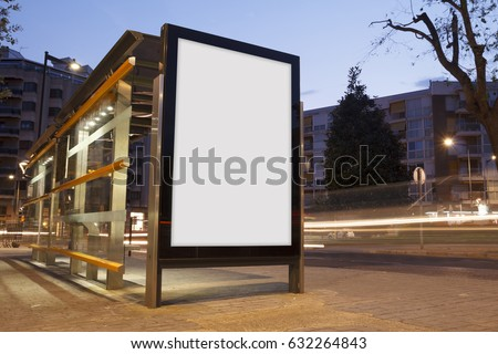Blank advertisement in a bus stop, with blurred traffic lights