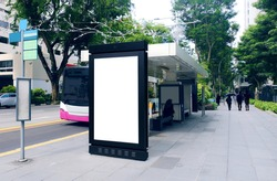 Blank advertising poster banner mockup at bus stop shelter by main road; out-of-home OOH vertical billboard media display space. Perspective angle