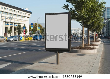 Blank advertizing billboard for commercials in city center. Pedestrian area near busy street with vehicles and cars. Administrative buildings, trees, road signs and multistoried houses in background.