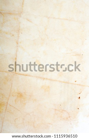 Blank aged paper sheet as old dirty frame background with dust and stains. Front view. Vintage and antique art concept. Detailed closeup studio shot. Toned #1115936510