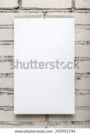 Blank album on a spring against a white brick wall. Template for design calendars and photo albums. Vertical shot.