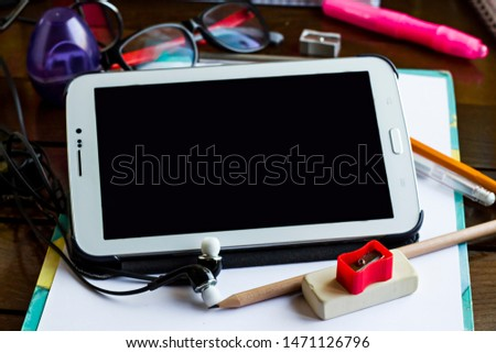 Blank and black screen of tablet on the student's desk with pencil,ruler,sharpener and headphone.Conceptual image of education.