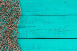 Blank antique teal blue aged wooden sign background with fish net border