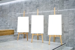 Blank art board canvas on wooden easels in exhibition gallery