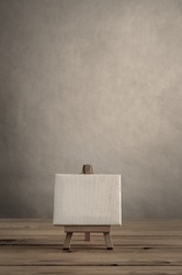 Blank art canvas on easel standing on wood plank floor.  Empty wall behind provides copy space above.