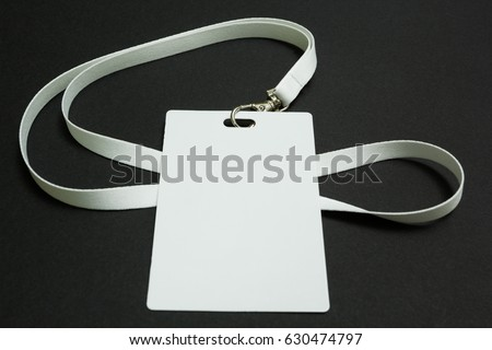 Blank badge mockup isolated on black. Plain empty name tag mock up hanging on neck with string. #630474797