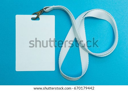 Blank badge mockup isolated on blue. Plain empty name tag with string. #670179442