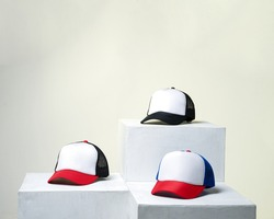 Blank baseball cap neatly displayed on a tiered stand. A plain hat on display for promo material. Arrangement concept that attracts customers to buy. Hat mockup for template design.