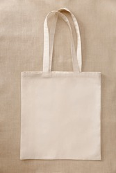 Blank beige mockup linen cotton tote bag on linen fabric. Eco nature friendly style. Environmental conservation recycling concept.