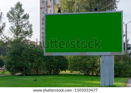 blank billboard, a large billboard on the background of the park and the street. Green mock ups isolated.