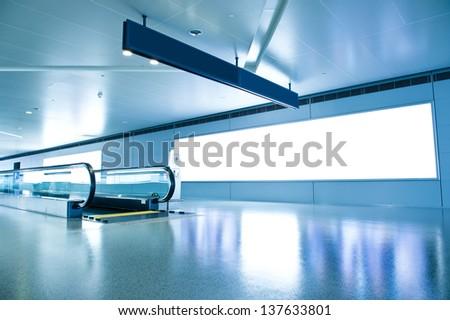 Blank billboard and modern escalator at a international airport