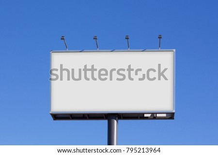 Blank billboard for advertising, against blue sky