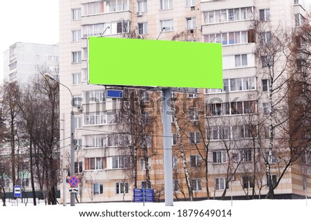 Photo of  Blank billboard for advertising on winter day, space for text, image, design. Large format outdoor advertising design with external illumination on high support. Banner, template. Chromakey