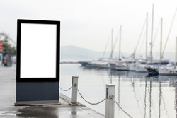 Blank billboard mock up, public information board with copy space on the street, near harbor. Empty banner for your advertising, clear poster in city with beautiful background (boats, yachts in pier)
