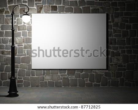 Blank billboard on a brick wall illuminated by streetlight