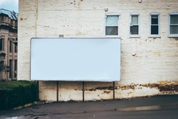 blank billboard on the side of building / advertising space place ad here blank space in parking lot white building editable