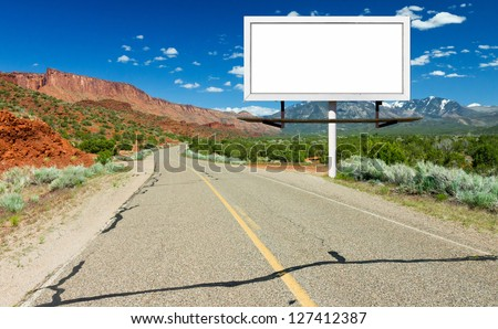 Blank billboard sign by empty highway through desert landscape