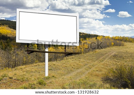 Blank billboard sign on dirt trail through a Fall aspen forest in the Colorado wilderness