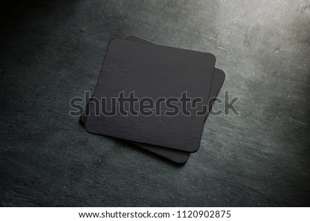 Blank black beer coaster stack mock up, top view, lying on the textured background. Squared clear can mat design mockup isolated. Quadrate cup rug display