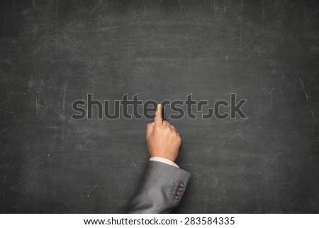Blank black blackboard with businessman hand pointing