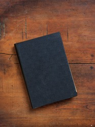 Blank black color book on wooden table background. Old vintage closed  hard cover book, cover template, top view, vertical