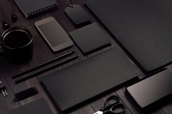 Blank black corporate stationery on dark stylish wood background, inclined. Branding mock up for branding, graphic designers presentations and business portfolios. Modern stylish work place.
