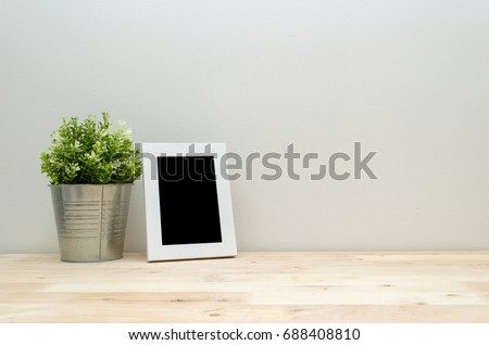 blank black frame mock up white picture frame with mini leaf green plant tree in silver pot small home decorative on wooden desk with white wall background, home decoration concept, copy space