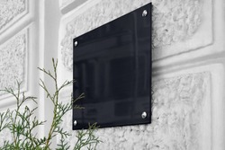 Blank black glass signboard on gray textured wall mockup. Empty hanging plexiglas nameplate mock up. Clear dark namesign on wal for corporate or store title mokcup template.