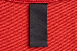 Blank black laundry care clothes label on red fabric texture background