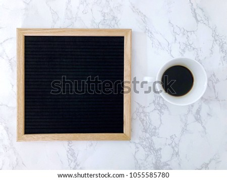 Blank black letter board with space for copy, black coffee, on white marble working desk. Flat lay. Top view.