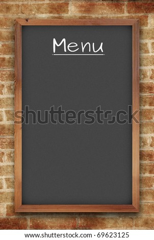 blank black menu chalkboard on brick wall - stock photo