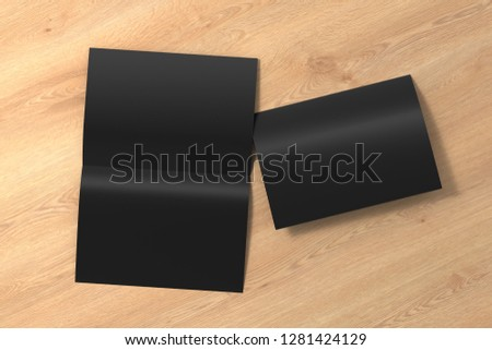 Blank black open and folded half-folded flyer leaflet on wooden background. With clipping path around brochure. 3d illustration