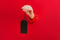 Blank black tag in female hand through a hole in red background. Price tag, gift tag, address label. Sale concept.