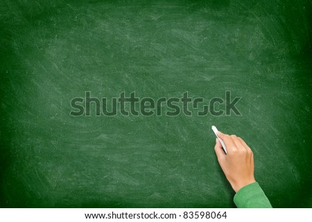 Blank blackboard / chalkboard. Hand writing on green chalk board holding chalk. Great texture for text. - stock photo