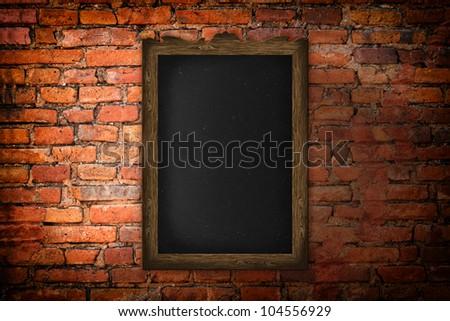 Blank blackboard on a brick wall background.