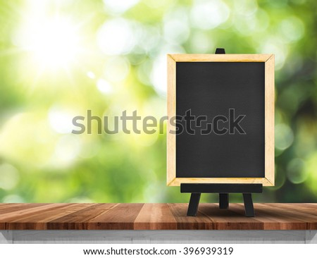 Blank blackboard on wood table top  with sun and blur green tree bokeh background, Template mock up for montage of product.