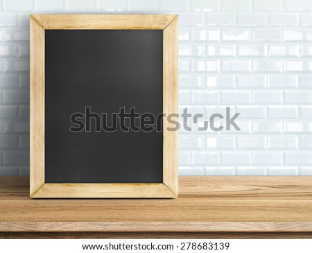 Blank blackboard on wooden table at white tile wall,Template mock up for adding your design and leave space beside frame for adding more text.