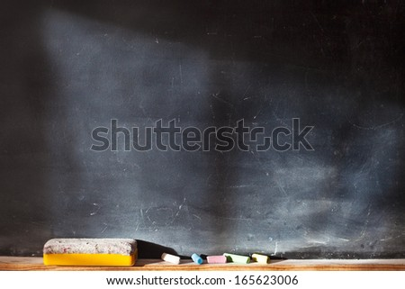 Blank blackboard with colored chalks and eraser and light effect. Horizontal composition.