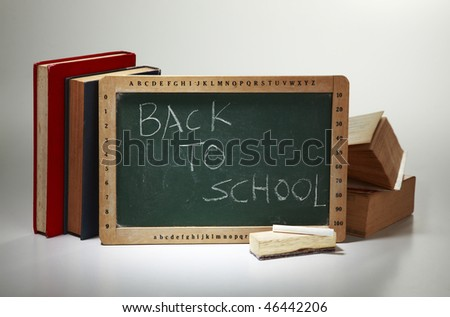 blank blackboard with the stack of book behind - stock photo