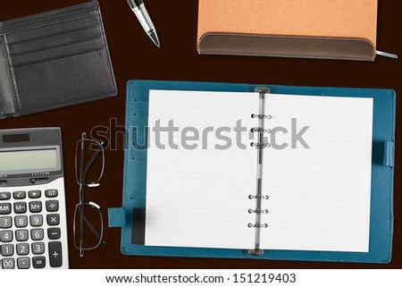 blank blue notebook & pocket card with stationery on the desk for your text or card